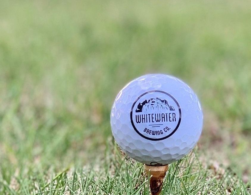 Whitewater Brewing Co. branded golf ball atop a wooden tee on a lush, green golf course