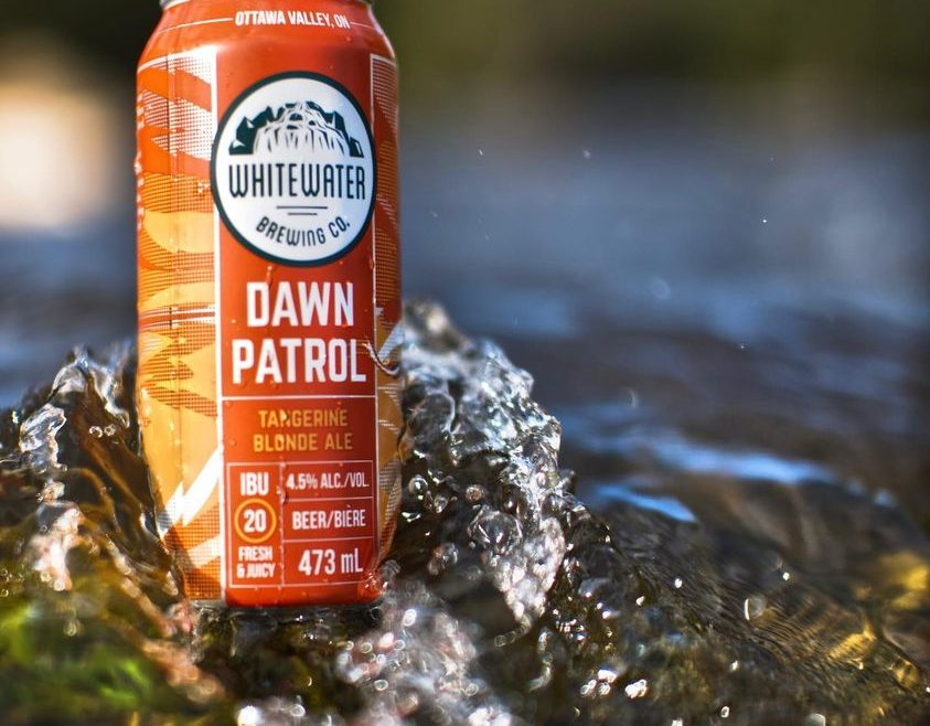 Can of Dawn Patrol sitting in Ottawa River with water crashing around it