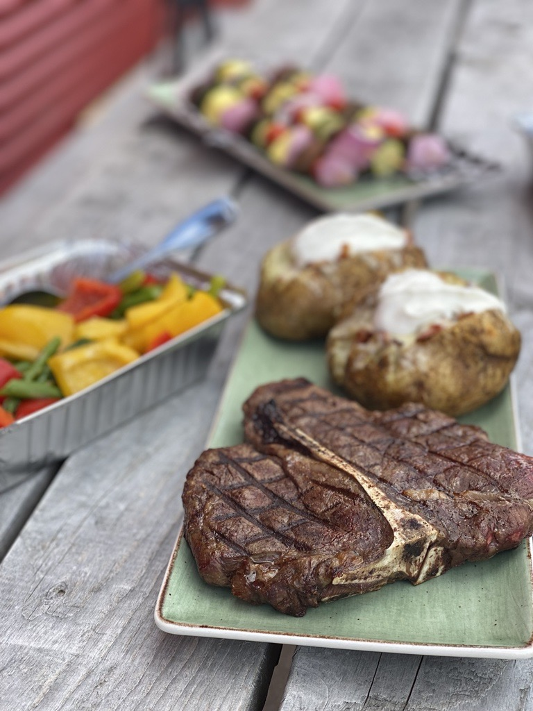 Porterhouse Steak with Baked Potatoes and side of grilled sweet peppers. Placed atop a picnic table.